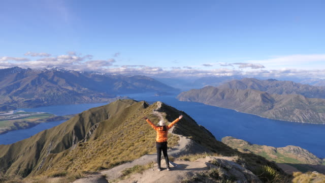 Hiking mountain Woman on the mountain top raising hands in sunset, Roys peak