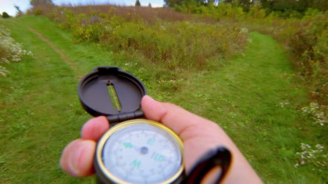 hiking point of view close up hand operating compass at fork in trail - kompass stock-videos und b-roll-filmmaterial