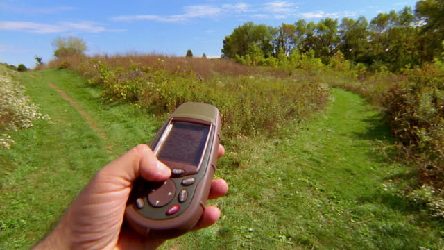 hiking point of view close up hand operating gps (global positioning system) at fork in trail - global positioning system stock videos & royalty-free footage