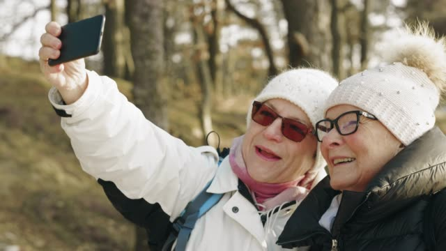 hiking senior couple are taking selfies - warm clothing stock videos & royalty-free footage