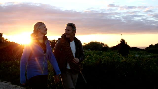vidéos et rushes de la randonnée et l'escalade couple marche le long de la piste au lever du soleil - couple d'âge mûr
