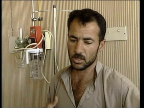 hillah int cms ali abed crying at hospital bed of injured 2 year old son 2 year old hussein lying heavily bandaged on bed father at bedside of... - al fallujah stock videos and b-roll footage