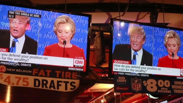 hillary clinton laughs at donald trump during their presidential debate which is projected onto televisions at nick's english hut in bloomington... - debatte stock-videos und b-roll-filmmaterial