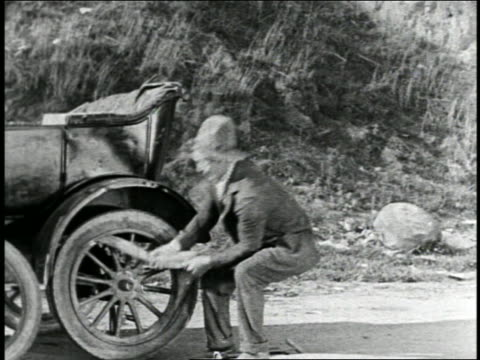 b/w 1925 hillbilly man pulling on inner tube of battered car on road / feature - 1925 stock videos & royalty-free footage