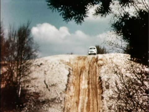 1957 ws td 1957 hillman minx driving down dirt hill and past camera / united kingdom - 1957 stock-videos und b-roll-filmmaterial