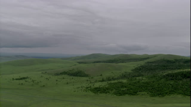 hills and grasslands cover the steppes in mongolia. available in hd. - mongolei stock-videos und b-roll-filmmaterial