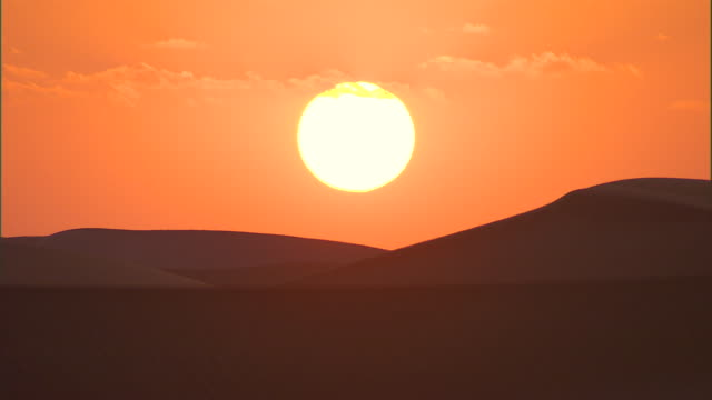 hills form silhouettes as the sun rises over the sahara desert. - desert stock videos & royalty-free footage