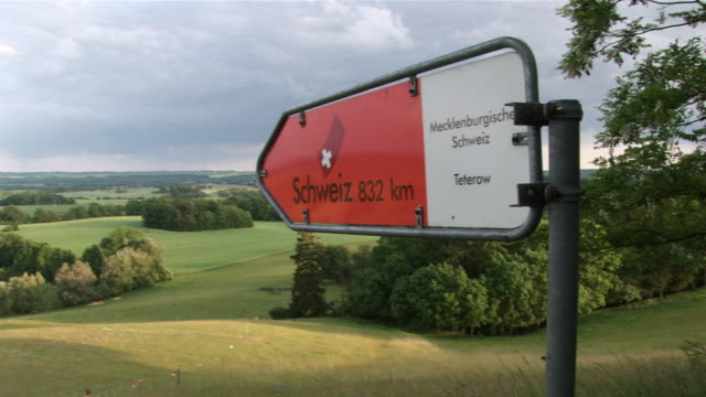 ws hills of mecklenburg switzerland sign pointing to switzerland / teterow, mecklenburg-western pomerania, germany - western script stock videos & royalty-free footage