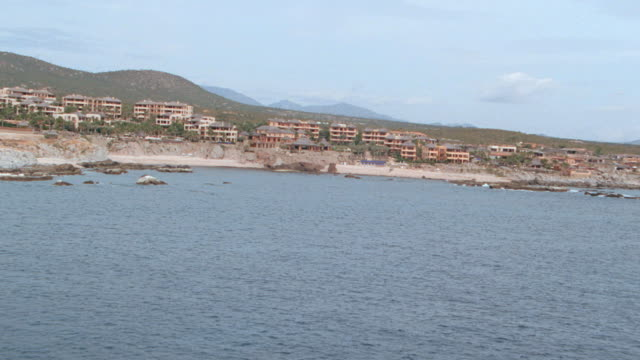 hills rise beyond the coastline. - cabo san lucas stock videos & royalty-free footage