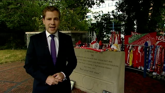 independent report reveals police cover up reporter to camera in front of memorial to those killed in hillsborough disaster scarves on fence and... - hillsborough disaster stock videos and b-roll footage