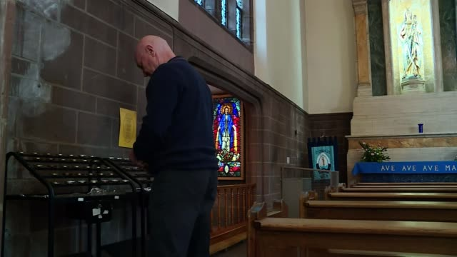 jury rules that 96 victims were unlawfully killed england merseyside int various of steven kelly lighting candle for his brother in chuch - ジャッキー ロング点の映像素材/bロール