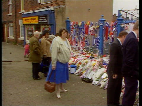 hillsborough disaster: private prosecution; lib england: yorkshire: sheffield: ext people looking at flowers and scarves left outside hillsdborough... - 準決勝点の映像素材/bロール