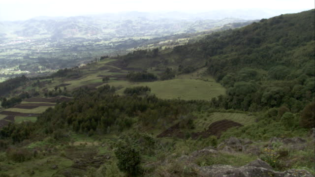 A hillside boundary of the Volcanoes National Park is located above an agricultural valley in Rwanda. Available in HD.