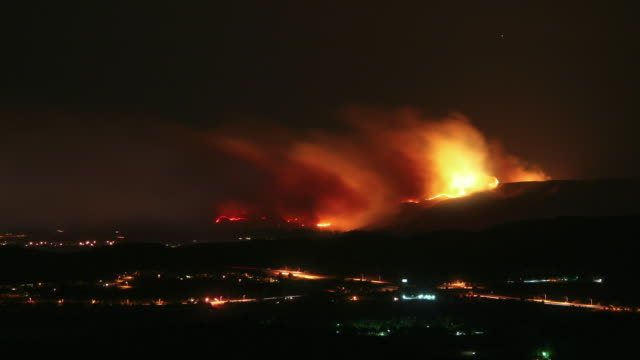 T/L WS HA Hillside fires, highway in foreground, night to day, Moorpark, California, USA