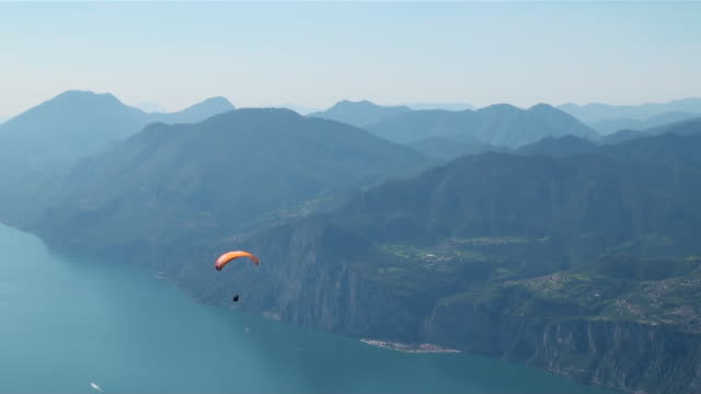 ws hillside paraglider over landscape lake and mountais / macesine, verona, italy   - paragliding stock videos & royalty-free footage