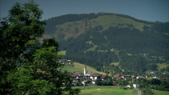 hillside & valley village w/ rounded mountain bg. - 北チロル点の映像素材/bロール