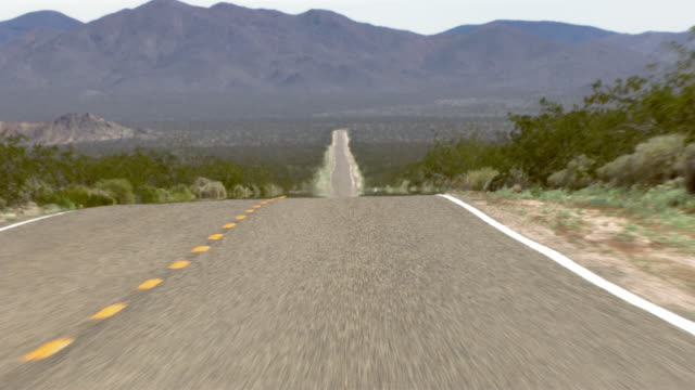 vídeos de stock, filmes e b-roll de a hilly highway cuts through the mojave desert. - plano geral ponto de vista