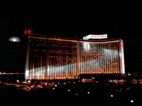 hilton hotel w/ searchlight beams moving over building, low altitude moving fast over paradise road & parking lot, steep ascent up & over hilton roof... - las vegas hilton stock-videos und b-roll-filmmaterial