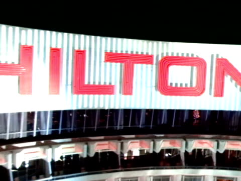 hilton hotel w/ searchlight beams moving over building, low altitude moving fast toward curved hilton hotel steep ascent up & over hilton roof sign.... - las vegas hilton stock-videos und b-roll-filmmaterial
