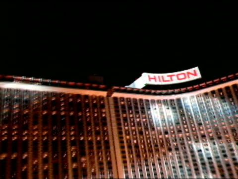 hilton hotel w/ searchlight beams moving over building, low altitude moving fast toward curved hilton hotel steep ascent up & over hilton roof... - las vegas hilton stock videos & royalty-free footage