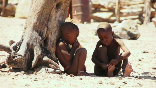 ms himba boys playing under tree with string and eating food / himba, kunene, namibia - wiese点の映像素材/bロール