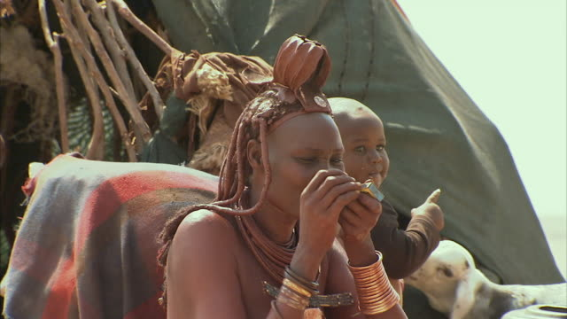 cu, himba tribeswoman smoking pipe outdoors, boy (12-17 months) and goat in background, namib desert, namibia - 12 17 months stock videos & royalty-free footage