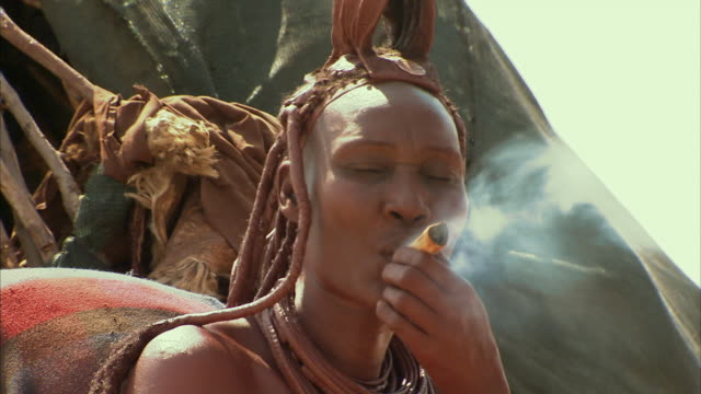 cu, himba tribeswoman smoking pipe outdoors, namib desert, namibia - zöpfchenfrisur stock-videos und b-roll-filmmaterial