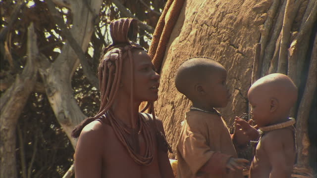 cu, himba tribeswoman with two children (12-17 months, 18-23 months) outdoors, namib desert, namibia - 12 23 mesi video stock e b–roll