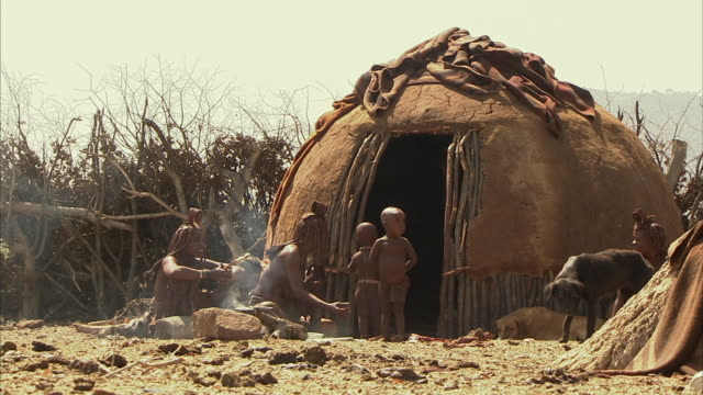 ws, himba tribeswomen with four children (12-17 months, 18-23 months, 2-3, 4-5) cooking in front of hut, namib desert, namibia - 12 23 mesi video stock e b–roll
