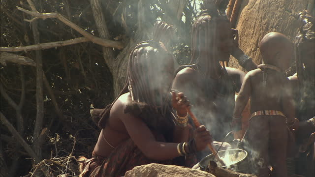 ms, himba tribeswomen with three children (12-17 months, 18-23 months, 4-5) cooking in front of hut, namib desert, namibia - 12 17 months stock videos & royalty-free footage