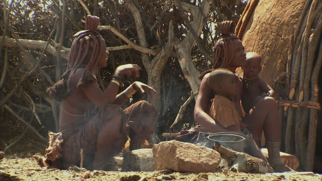 ms, himba tribeswomen with two boys (12-17 months, 18-23 months) in front of hut, namib desert, namibia - 12 23 mesi video stock e b–roll