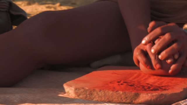 A Himba woman grinds seeds with a rock in Namibia. Available in HD.