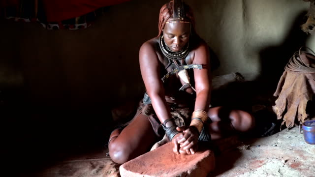 Himba woman makes powdered Okra for body and hair coloring , Namibia