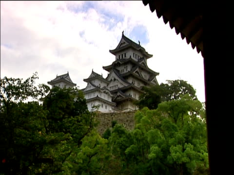 himeji castle surrounded by trees seen from distant entrance porch japan - 城点の映像素材/bロール