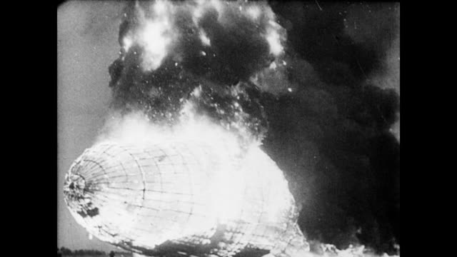 / hindenburg airship bursts into flames / flames and smoke rise as the ship turns and begins to fall out of the sky / people screaming as the fiery... - airship stock videos & royalty-free footage