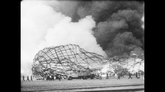 / Hindenburg airship lies on the airfield a flaming wreck / plumes of black and white smoke rise from the pile of twisted metal framework / more and...