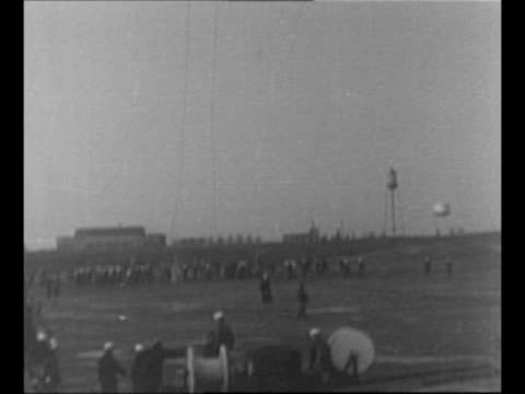 Hindenburg approaches soggy landing field with ground crew waiting in background and puddles in foreground / Hindenburg drops mooring ropes tilt down...