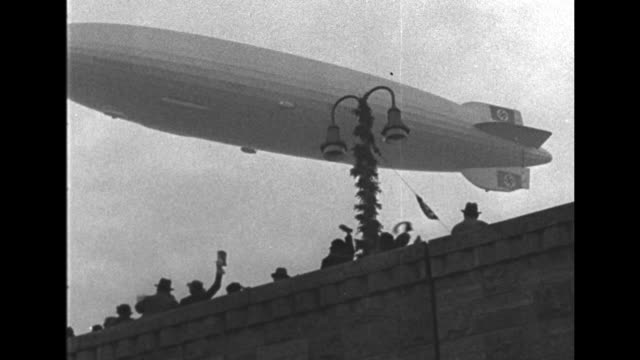 'Hindenburg' flying overhead / WS 'Hindenburg' flying past buildings on shore of Rhine River / 'Hindenburg' flying over Rhine River / Nazi flag in...