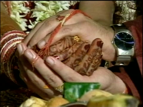 hindu bride and groom sit smiling and holding hands during wedding ceremony new delhi - cross legged stock videos & royalty-free footage