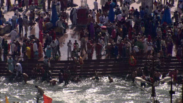 hindu devotees gather in and around the ganges to perform ritualistic bathing. - ヒンズー教点の映像素材/bロール