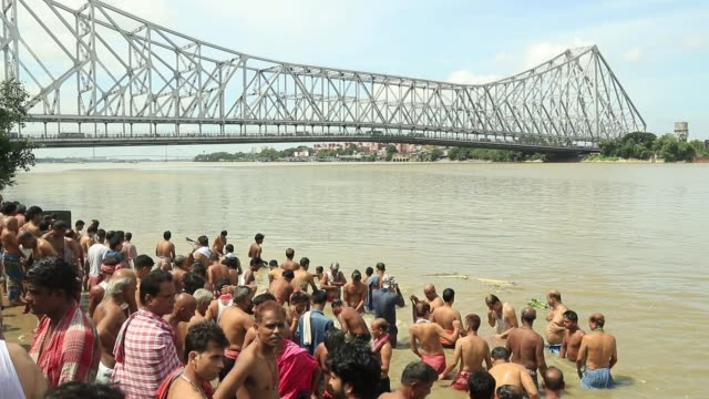 hindu devotees perform the 'tarpan' ritual to pay obedience to their ancestors on the last day of hindu event 'pitru paksha' near the howrah bridge... - howrah bridge stock videos & royalty-free footage