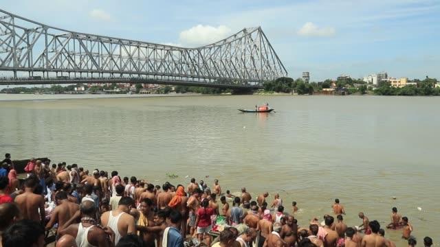 hindu devotees perform the 'tarpan' ritual to pay obedience to their ancestors on the last day of hindu event 'pitru paksha' near the howrah bridge... - howrah bridge stock videos & royalty-free footage