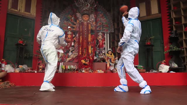 vidéos et rushes de hindu devotees wearing personal protective equipment perform dhunuchi , a traditional dance, in front of an idol of hindu goddess durga during durga... - fête religieuse