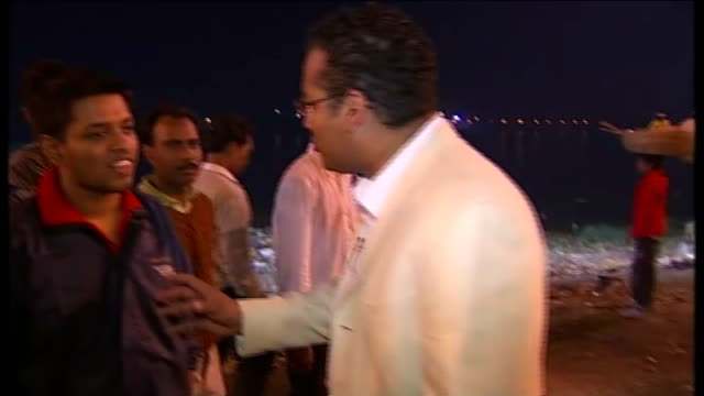 west bengal kolkata ext reporter interviews devotees gathered by river hoogly as devotees gather for hindu festival of saraswati sot statue of... - west bengal stock videos and b-roll footage