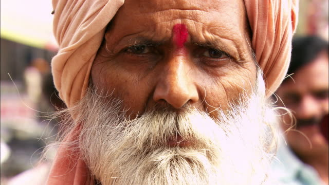 a hindu man wears a traditional turban. available in hd. - turban stock videos & royalty-free footage