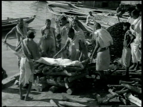 vidéos et rushes de funeral hindu men placing wrapped body on logs by ganges river funeral pyre smoking pyre w/ sticks covering body - 1942