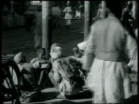 vidéos et rushes de hindu people walking sidewalk next to sacred cattle men crouching talking at sidewalk edge near nursing sheep w/ people walking fg men w/ baby male... - 1942