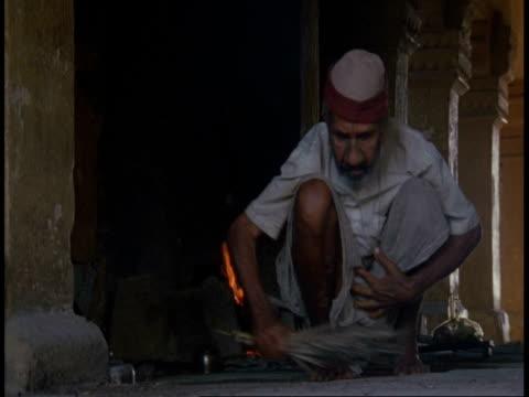 vídeos y material grabado en eventos de stock de ms hindu priest sweeping up dust in temple, bandhavgarh national park, india - un solo hombre mayor