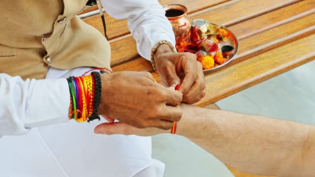 hindu priest tying a holy thread on worshipper's wrist - worshipper stock videos and b-roll footage