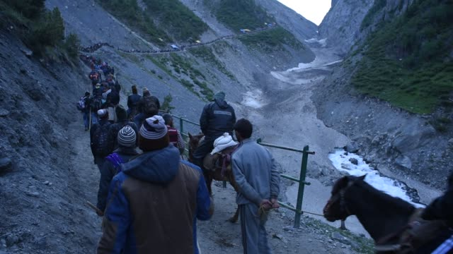 hindu walk on mountain trails on foot ponies and are being carried in the palanquins as they make their pilgrimage to the sacred amarnath caves one... - stalagmite stock videos and b-roll footage